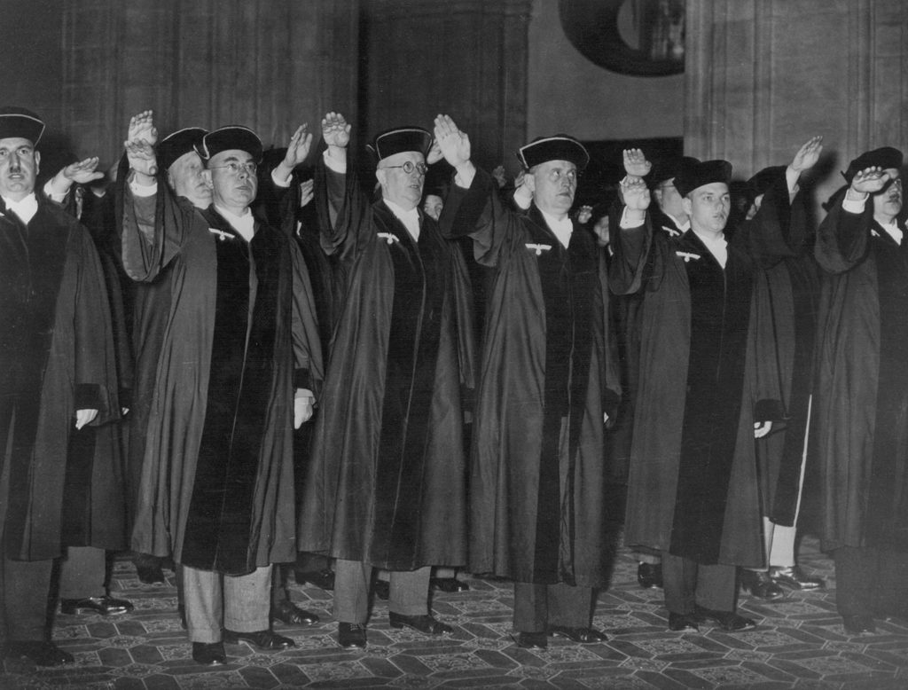 A large group of judges wearing their robes give the Nazi salute as they pledge their loyalty to the Nazi Party in Berlin.