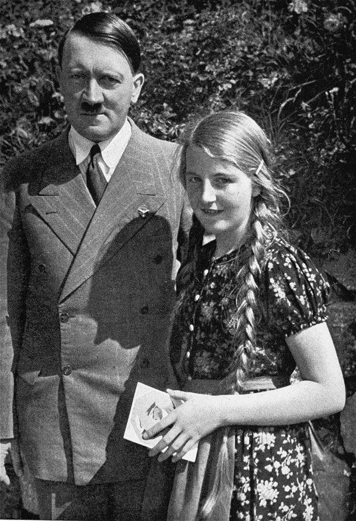 Hitler stands next to a young smiling girl wearing a floral dress with long blonde braids.