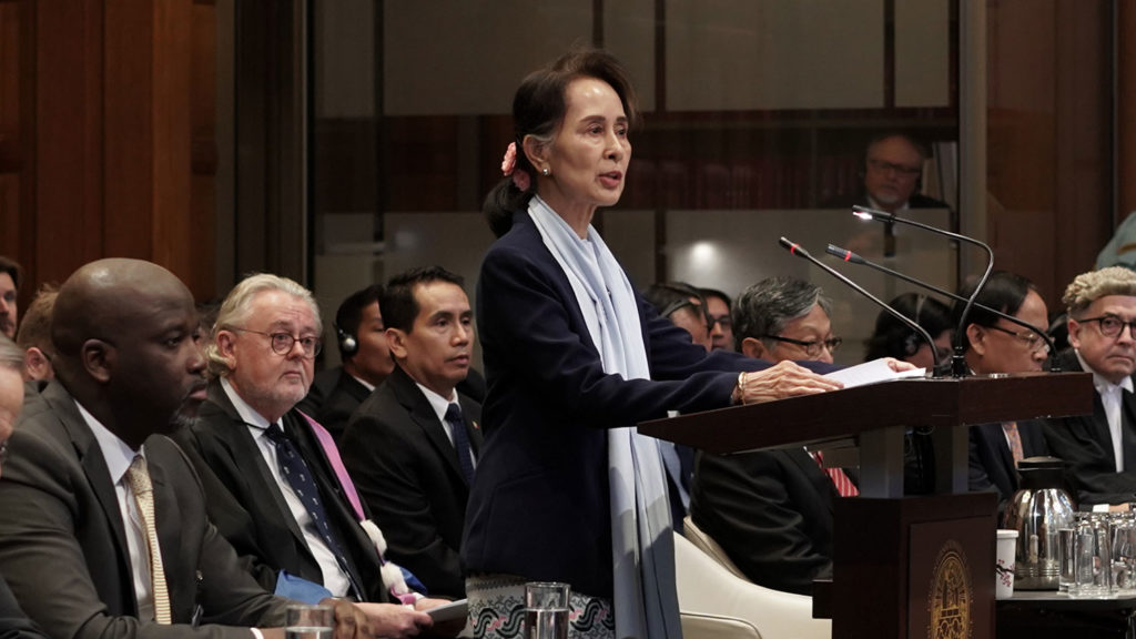Aung San Suu Kyi stands before the International Court of Justice to defend Myanmar, stating that accusations of genocide against the country's Muslim Rohingya minority are unfounded. She is surrounded by other politicians as she stands at the podium.