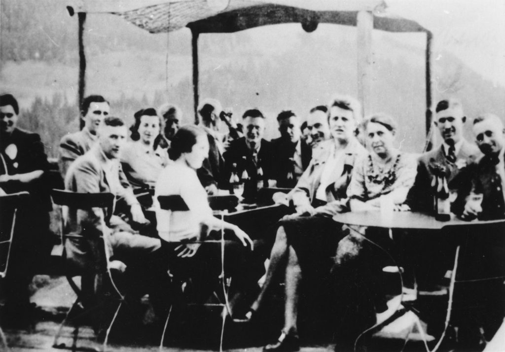 Staff of the T4 / euthanasia murder programme sit around tables on a holiday at the office's resort in the Austrian Alps. The Alps can be seen behind the gathering of male officers with their girlfriends and wives.