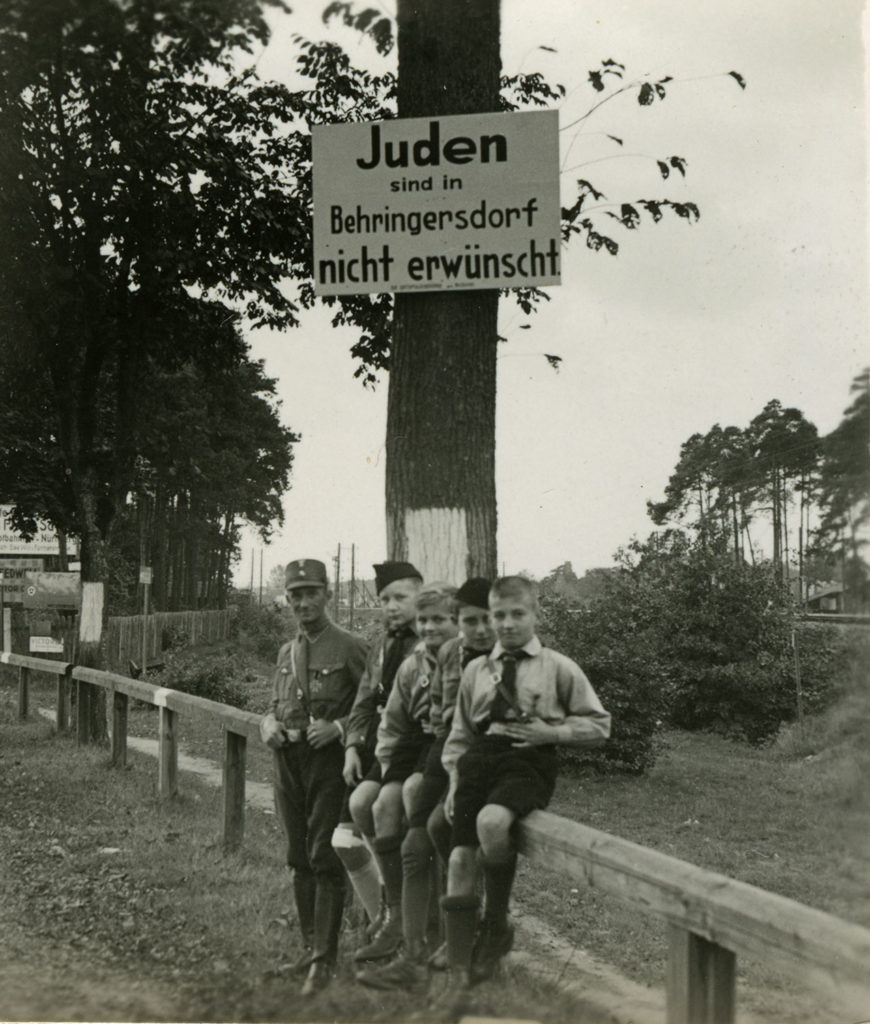 "A group of young uniformed Hitlers Youth (around 10 years of age) stand beneath a pole bearing the sign ""Juden sind in Behringersdorf nicht erwünscht"" (translated: Jews not welcomed in Behringersdorf)."
