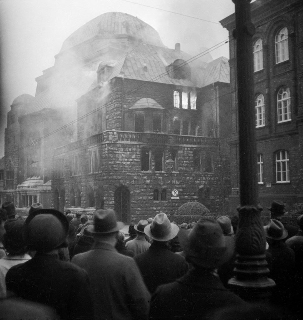 A large, dense crowd of Germans gathers to watch the Steeler Strasse synagogue in Essen burn on Kristallnacht (the 'night of broken glass').
