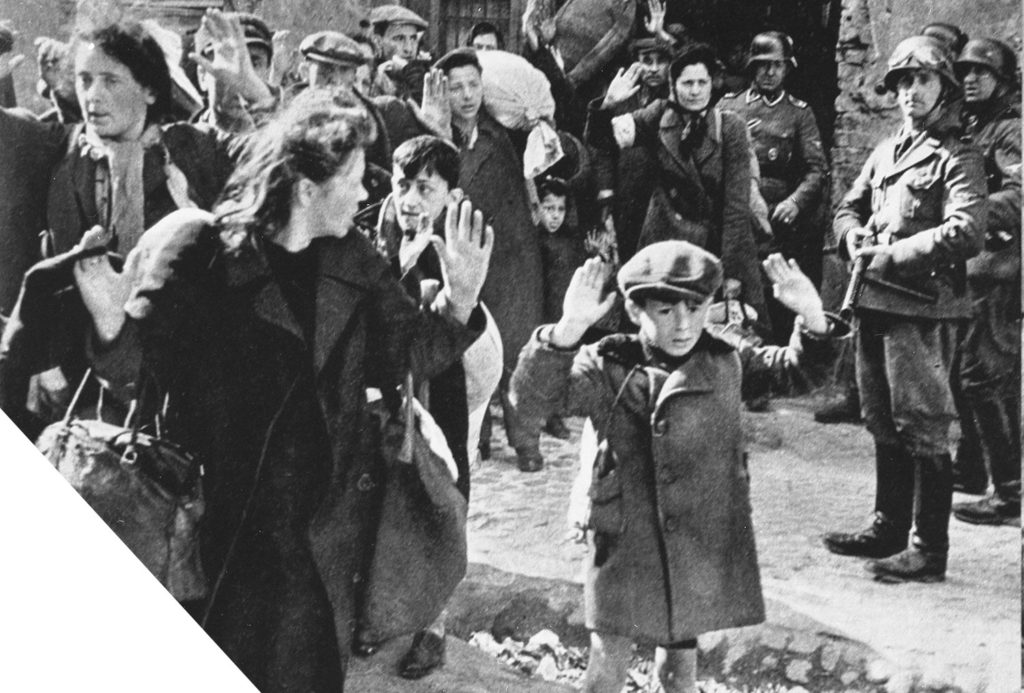 German soldiers point guns at young children, women, the elderly, and men during the Warsaw ghetto uprising as they round everyone up for deportation to concentration camps. Some people carry bags of their meager belongings. A young boy of 7 or 8 stands in the foreground, his arms above his head as an officer holds a rifle to his back.