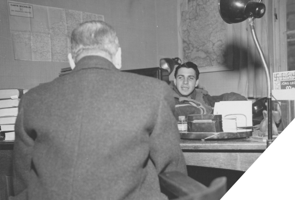 A young Allied officer interrogates a German citizen for information. The two sit at a desk in an office with maps on the walls. A book bearing a pattern of the Nazi symbol is in the far right frame of the image.